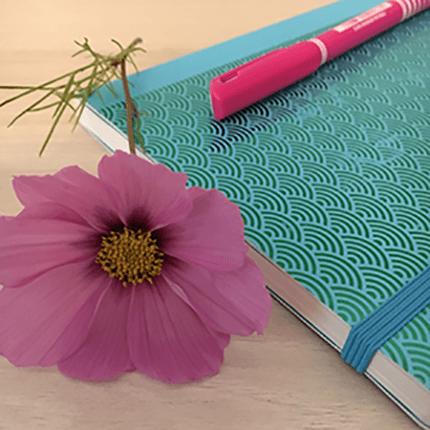 Notizheft mit Stift und einer Blume