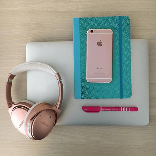 Laptop mit einem Kopfhörer, Notizbuch, Smartphone und einem Stift