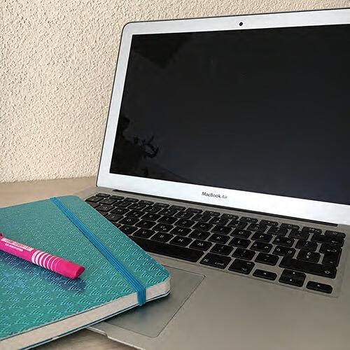 Geöffneter Laptop mit Heft und Stift