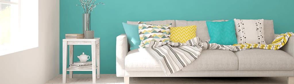 Sofa mit bunten Kissen vor einer Türkisfarbener Wand